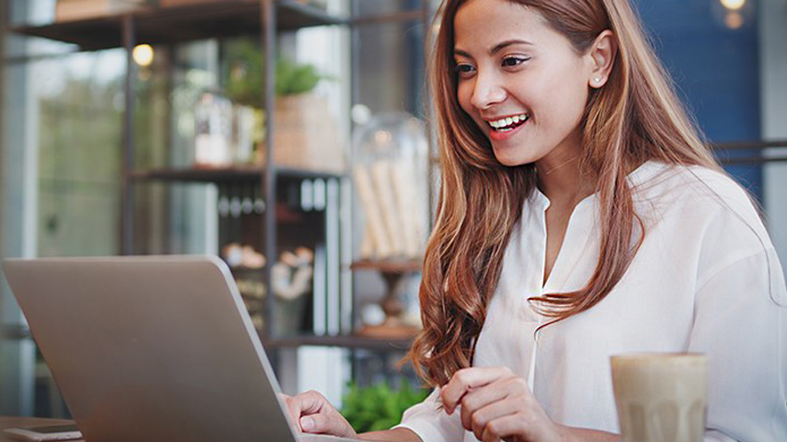 a woman using laptop in a coffee shop; image used for HSBC Vietnam Online Banking page
